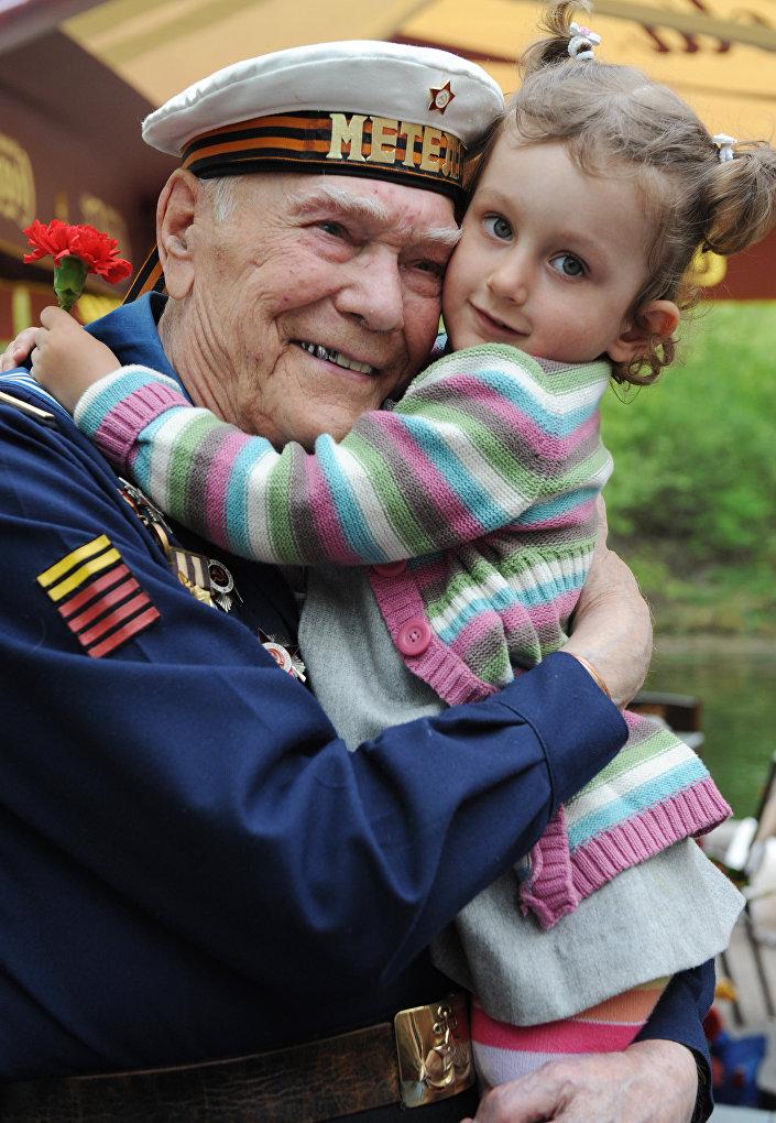 Un veterano della Grande Guerra Patriottica tiene in braccio una bambina.