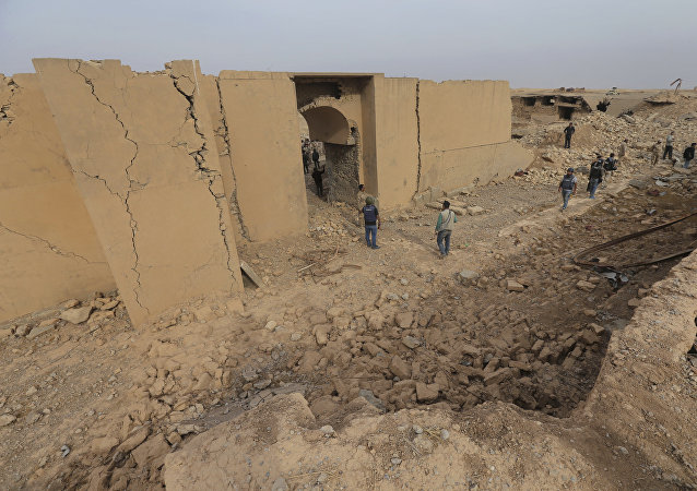 Iraqi soldiers and journalists walk in the damaged ancient site of Nimrud, which destroyed by the Islamic State militants, some 19 miles (30 kilometers) southeast of Mosul, Iraq, Wednesday, Nov. 16, 2016.