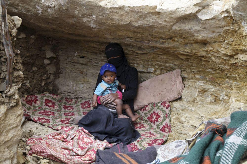 Una donna con un bambino si nasconde in una cava per scampare i bombardamenti.
