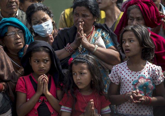 La preghiera di nepalesi sopravvissuti dopo il sisma