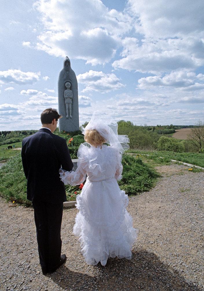 Una coppia di sposi davanti al monumento a Sergej Radonezh.