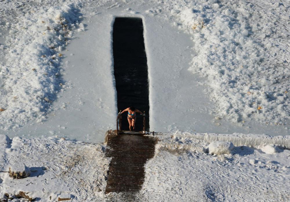 Una donna nella piscina nel ghiaccio alla costa del Golfo dell'Amur nell'Estreme Oriente della Russia.