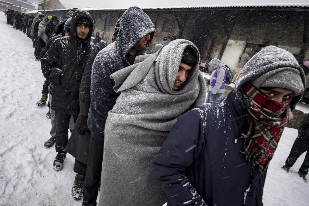 Migranti fanno la coda per cibo a Belgrado.