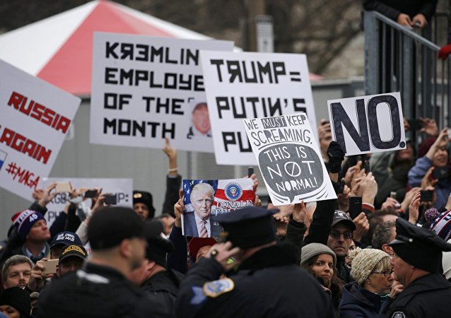People hold signs as they line the parade route waiting to see U.S. President Donald Trump in the inaugural parade in Washington, U.S., January 20, 2017