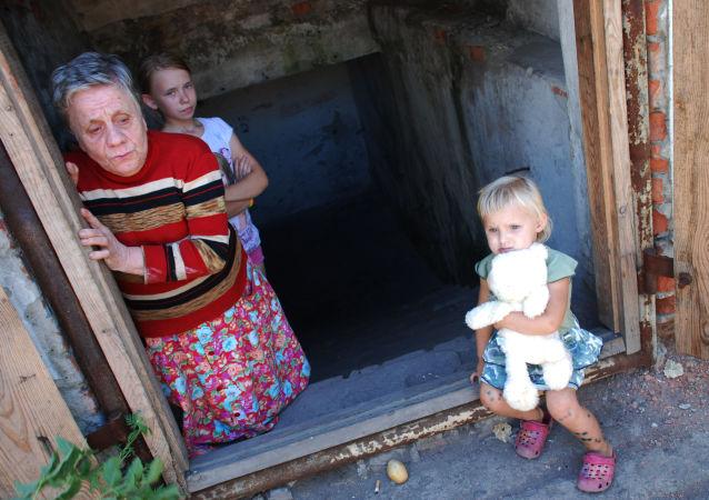 Bambini e una donna che vivono in un rifugio antiaereo in uno dei quartieri nella periferia di Donetsk.