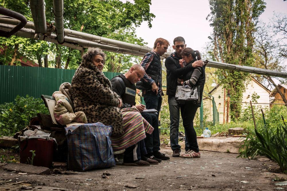 Gli abitanti di un edificio distrutto nei bombardamenti a Donetsk.