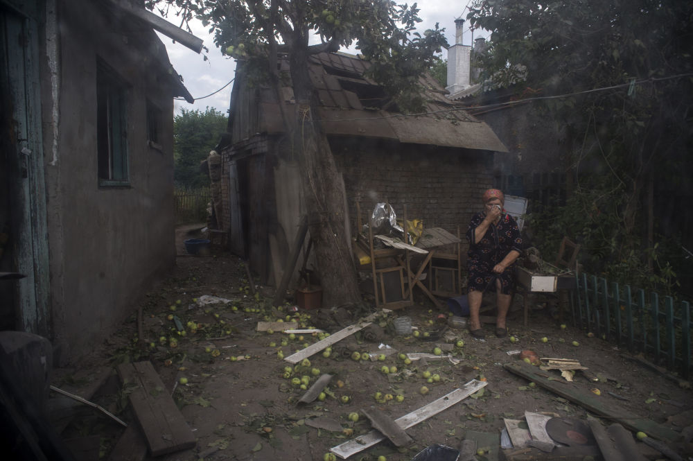 Una abitante di Lugansk vicino ad una casa distrutta dai bombardamenti delle forze ucraine.