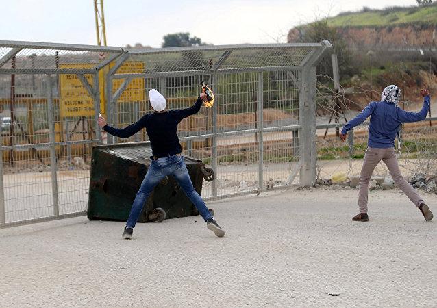Dimostranti palestinesi lanciano molotov contro oggetto israeliano