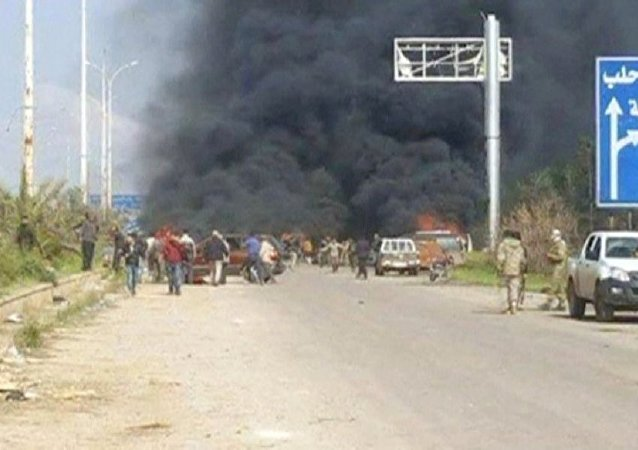 Image shows a cloud of black smoke rising from vehicles in the distance in what is said to be Aleppo's outskirts, Syria