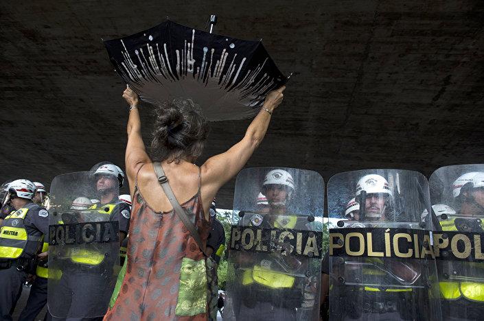Un manifestante protesta per la mancanza d'acqua di fronte alla polizia in Brasile.