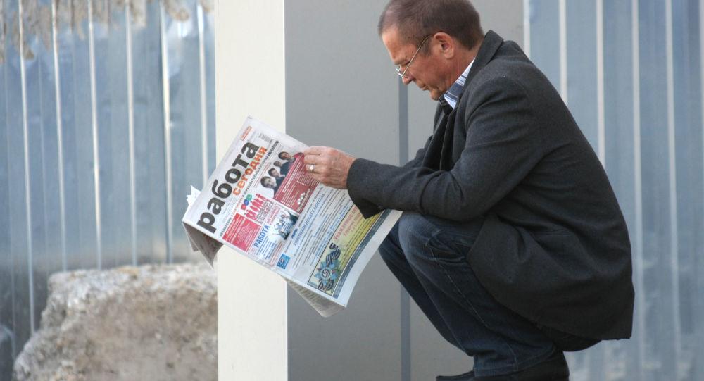 Un uomo cerca una proposta di lavoro in un giornale.