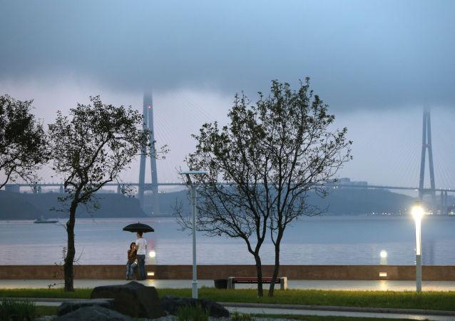 I giovani di sera sul lungomare dell'isola Russkij a Vladivostok sullo sfondo del ponte strallato sullo stretto del Bosforo orientale