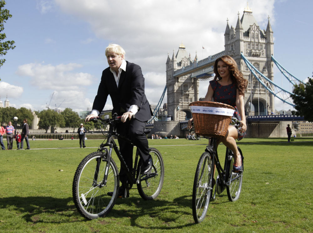 L'ex sindaco di Londra Boris Johnson e l'attrice Kelly Brook in bicicletta a Londra.