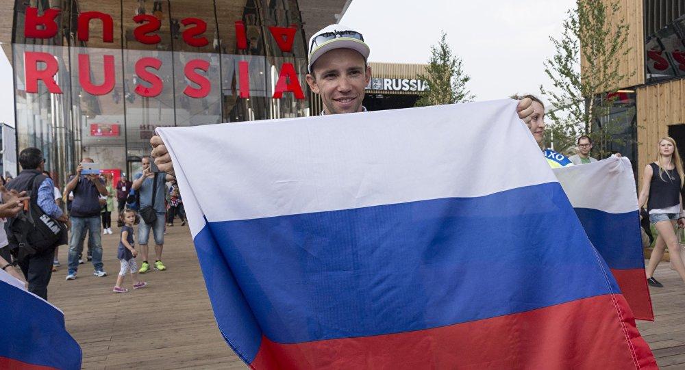 Un visitatore con la bandiera della Russia posa davanti al padiglione russo dell'EXPO di Milano