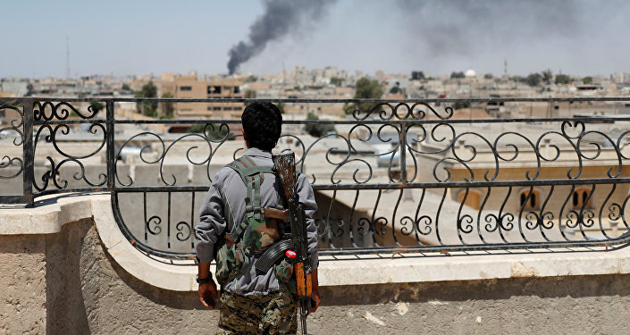A Kurdish fighter from the People's Protection Units (YPG) looks at a smoke after an coalition airstrike in Raqqa, Syria June 16, 2017