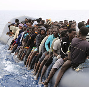 Migrants wait to be rescued from a sinking dingey off the Libyan coasal town of Zawiyah, east of the capital, on March 20, 2017, as they attempted to cross from the Mediterranean to Europe.