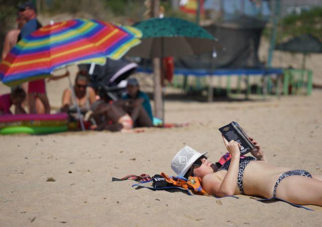 Vacationers on a beach on Bugazskaya Spit in Veselovka village