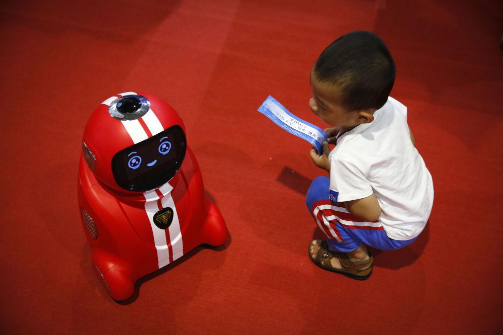 Un bambino osserva un robot ad autoapprendimento alla Conferenza Mondiale di Robotica a Pechino, Cina.