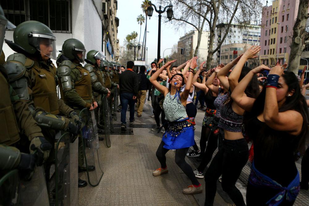 Manifestanti stanno ballando di fronte ai poliziotti durante la marcia per cambiare il sistema d'istruzione a Santiago, Cile.
