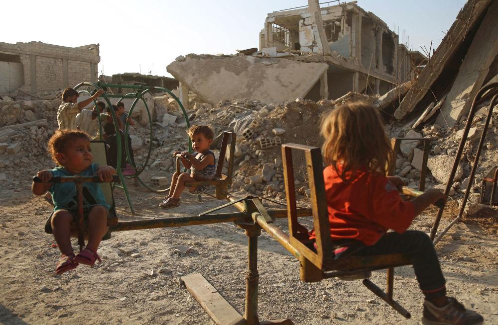 Bambini giocano in un quartiere distrutto della città siriana di Duma.
