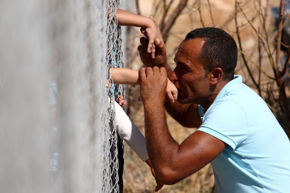 Ammar Hammasho, un siriano che abita in Cipro, bacia i suoi bambini che sono arrivati al campo dei rifugiati nei pressi di Nicosia.