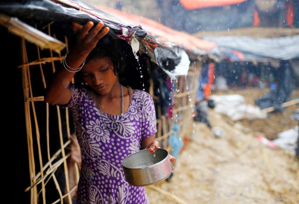 Una ragazza rifugiata raccoglie l'acqua di pioggia in Bangladesh.