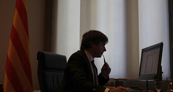 Catalan regional President Carles Puigdemont works on his speech at his desk inside the Palau de la Generalitat in Barcelona, Spain, Tuesday Oct. 10, 2017, which is the seat of the Catalan government.