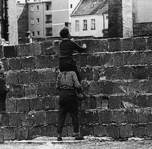 Un bambino sulle spalle di un altro bambino guarda oltre le mura che dividevano Berlino Ovest da Berlino Est