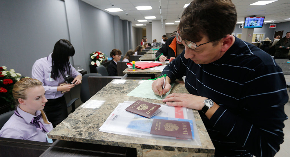 A visitor files papers at Visa Application Center