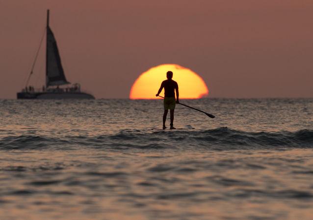 Serfer al tramonto nel Pacifico.