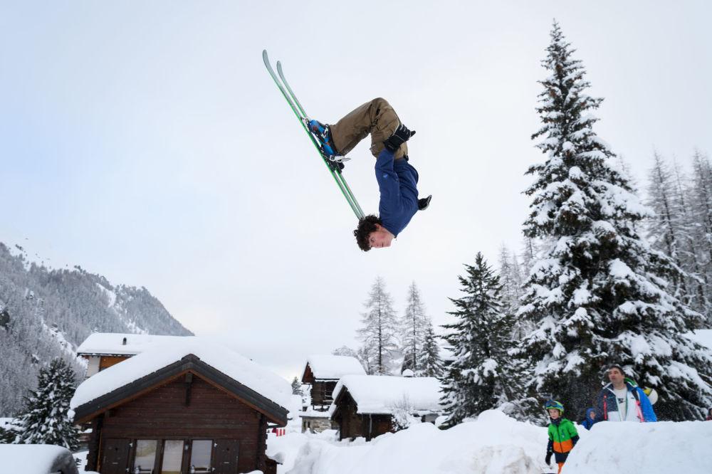 Un ragazzo fa un salto con gli sci nelle Alpe di Svizzera.