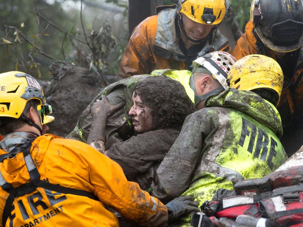 I soccorritori salvano una donna da sotto la sua casa destrutta a causa di una frana a Montecito, California, USA.
