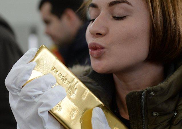 Una ragazza bacia un lingotto d'oro appena coniato dalla fabbrica Renova di Ekaterinburg
