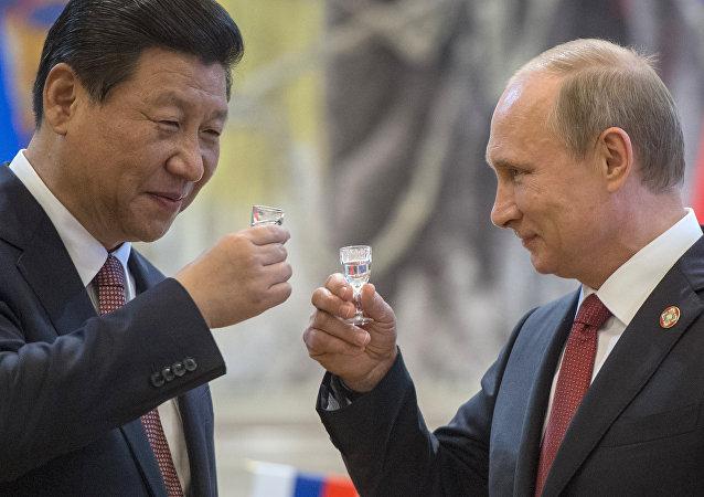 Vladimir Putin brinda con Xi Jinping