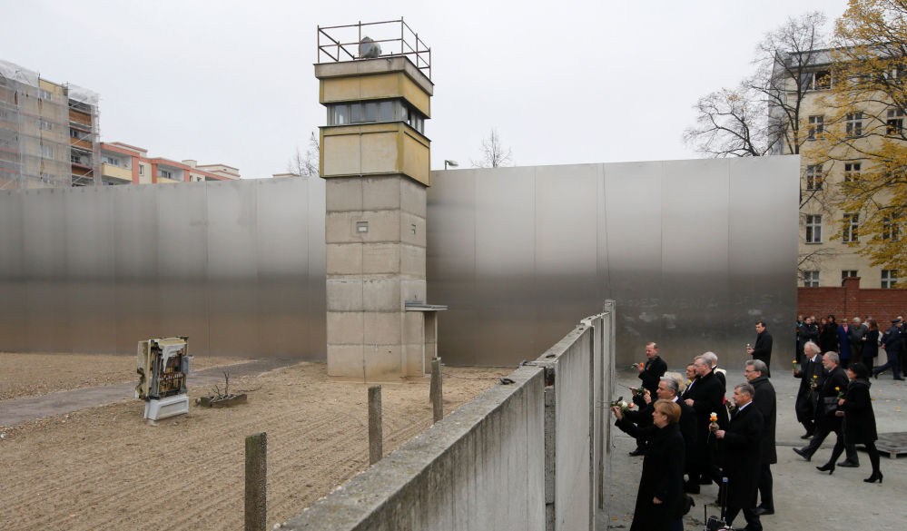 La cancelliera tedesca Angela Merkel depone fiori al Muro di Berlino.