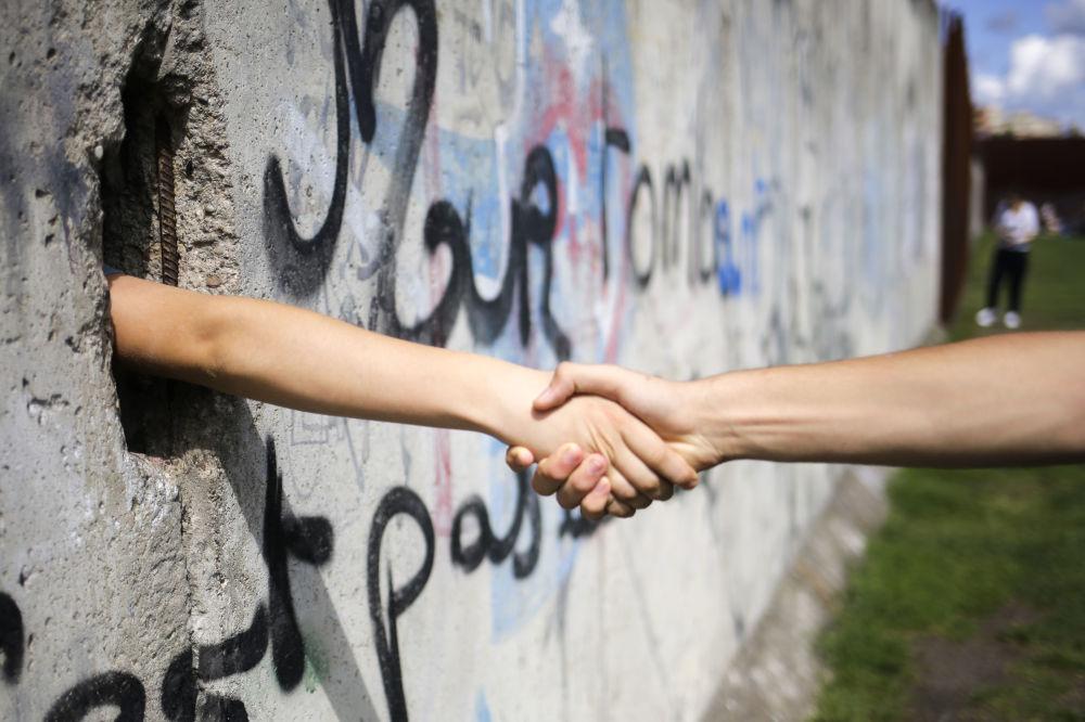 Turisti si stringono le mani tra il Muro di Berlino.