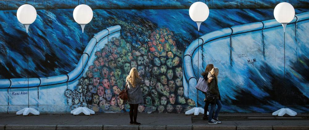 La gente sta vicino ai stand colorati con palloni luminosi, un'installazione al posto dove si trovava il Muro di Berlino.