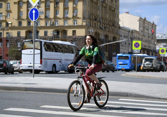 Una ragazza attraversa in bicicletta una strada di Mosca