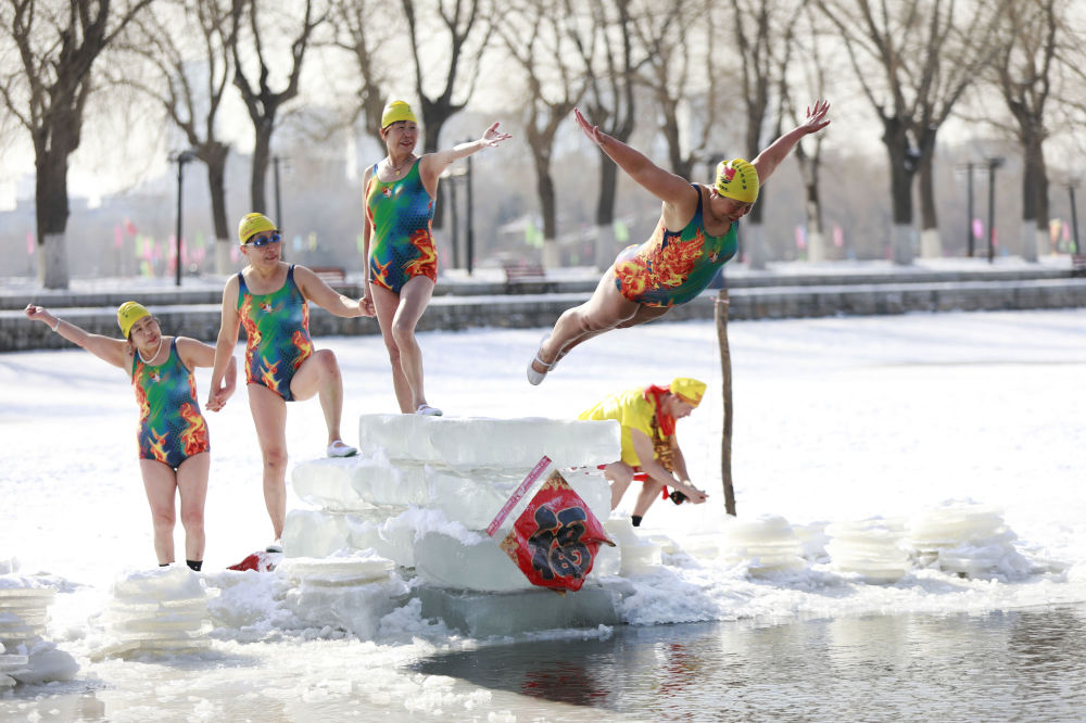 Una donna si tuffa nel lago parzialmente ghiacciato nella provincia cinese di Liaoning.