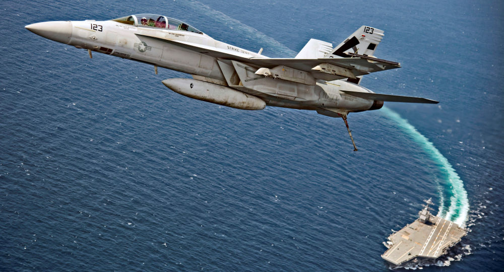 An F/A-18F Super Hornet jet flies over the USS Gerald R. Ford as the U.S. Navy aircraft carrier tests its EMALS magnetic launching system, which replaces the steam catapult, and new AAG arrested landing system in the Atlantic Ocean