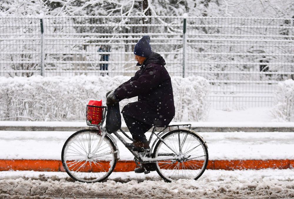 Un uomo va in bicicletta a Shenyang, Cina.