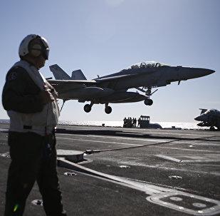 Un marines osserva l'atterraggio di un F/A-18 Super Hornet da una portaerei americana