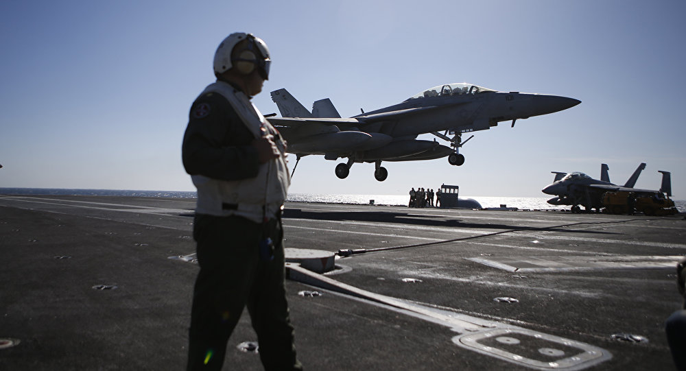 A US Navy crew member looks at an F/A-18 Super Hornet fighter landing onto the deck of the USS Ronald Reagan, a Nimitz-class nuclear-powered aircraft carrier, during a joint naval drill between South Korea and the US in the West Sea off South Korea on October 28, 2015
