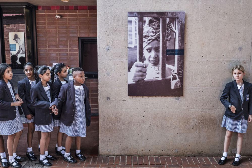 Le allieve di Sud Africa viste al cartellone che raffigura la ex moglie di Nelson Mandela sul muro della sua casa a Soweto.