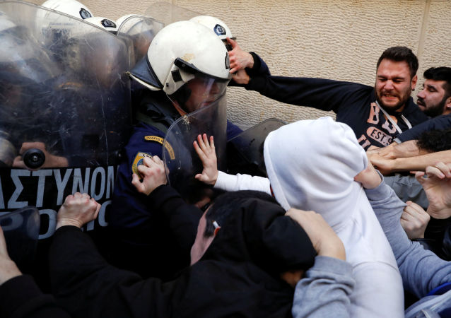 Demonstrators scuffle with riot police officers during a protest outside a notary's office to prevent an e-auction of repossessed properties in Athens, Greece