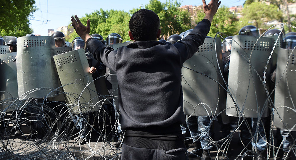 A demonstrator argues with riot police during a protest against Armenia's ruling Republican party's nomination of former President Serzh Sarksyan as its candidate for prime minister, in Yerevan, Armenia April 16, 2018.