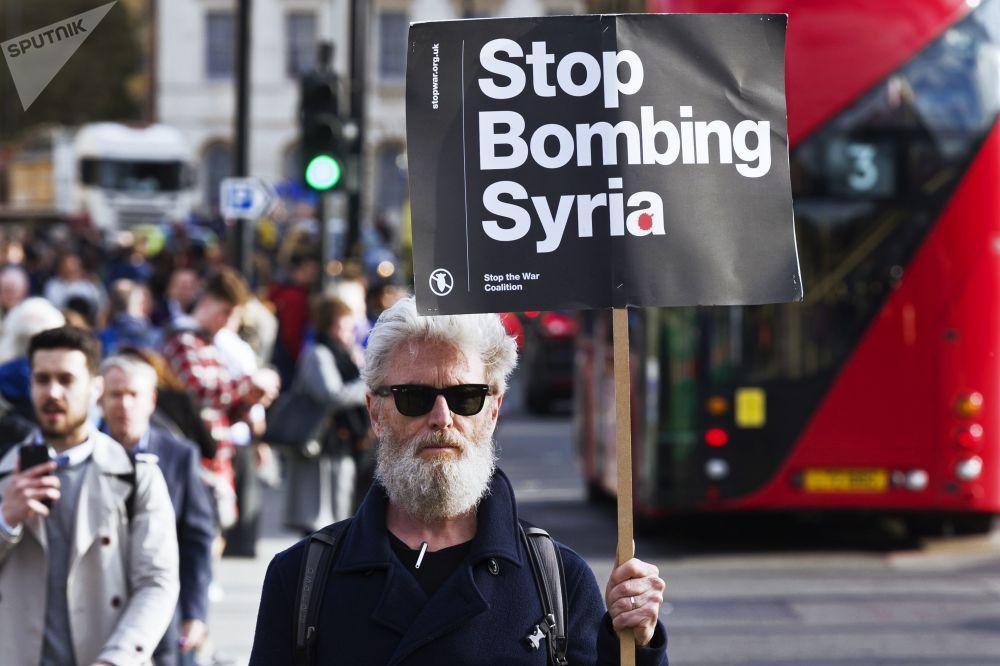 Un uomo tiene un cartello contro i bombardamenti in Siria alle proteste a Londra.