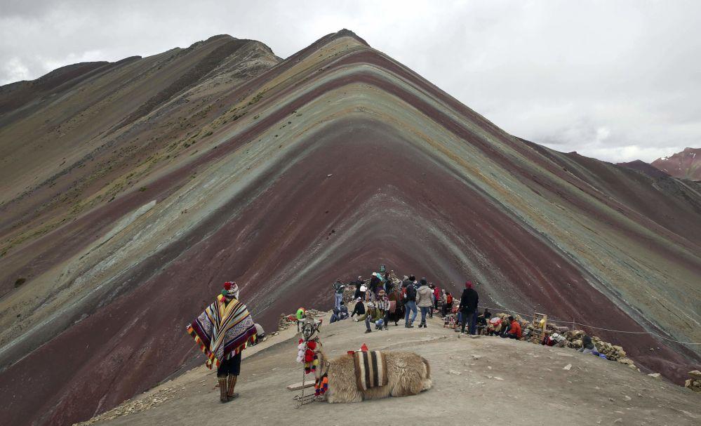 Un locale delle Ande con un lama e turisti stanno vicino alla Montagna Arcobaleno di Vinicunca in Perù.