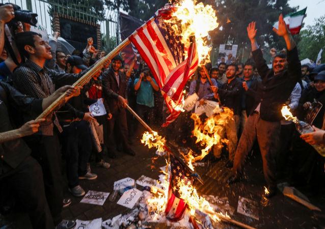 La bandiera statunitense viene bruciata durante le proteste a Teheran, Iran