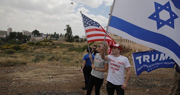 Gli israeliani tengono le bandiere degli USA e dell'Israele di fronte alla nuova ambasciata USA a Gerusalemme.